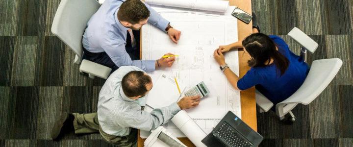 riunione intorno ad una scrivania; sulla scrivania planimetria e computer