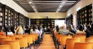 sala biblioteca con sedie arancioni in riunione